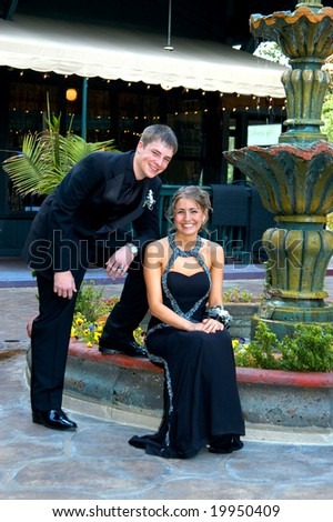 Teen couple sit outdoors at a water fountain dressed and ready for prom night.  Tux and gown both in black.