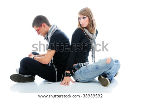 Teen couple sitting down with sad expression on their faces, isolated on white