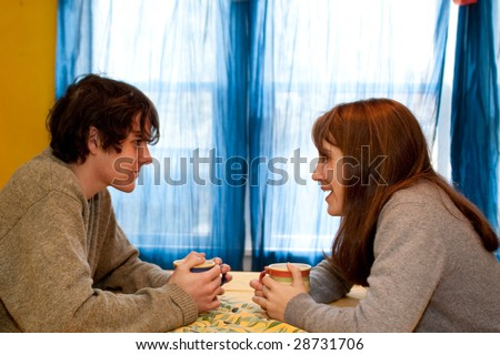 Teen couple talking over coffee or tea, at a yellow table.