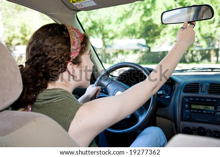 Teen driver adjusting her rear view mirror in the car.