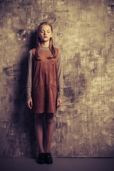 Teen fashion. Portrait of a cute girl teenager standing by a grunge wall.
