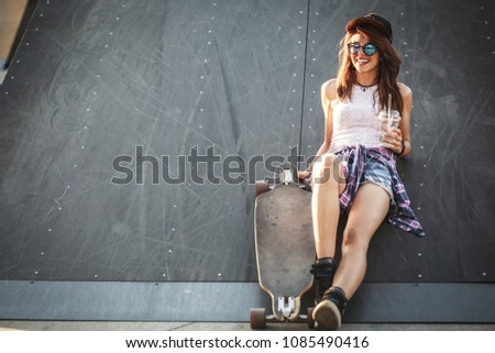 Teen female skater sitting on ramp at the skate park . #1085490416