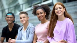 Teen friends smiling camera sitting outdoors, youth generation, happy classmates