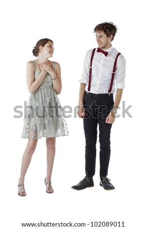 Teen girl and boy dressed formally for a prom look at each other with pleased expressions. Vertical, isolated on white, copy space.