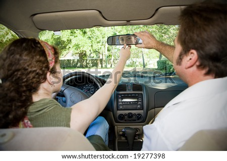Teen girl and her driving instructor adjusting rearview mirror.  Focus on girl in the mirror.