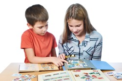 Teen girl and little boy with magnifying glass looking his stamp collection isolated white