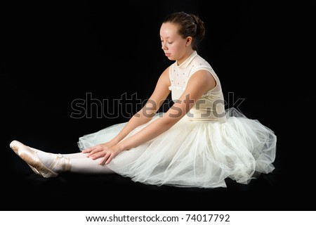 teen girl ballet dancer sitting in a tutu in points on a black background