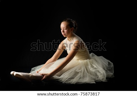 teen girl ballet dancer sitting in a tutu in points on a black background stretching