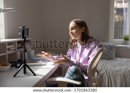 Teen girl blogger influencer recording video blog concept speaking looking at smartphone on tripod at home table. Teenager social media vlogger shooting vlog, streaming online podcast on mobile phone.