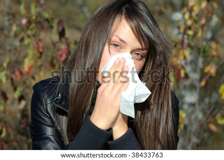 Teen Girl blowing her nose outdoors in late autumn.
