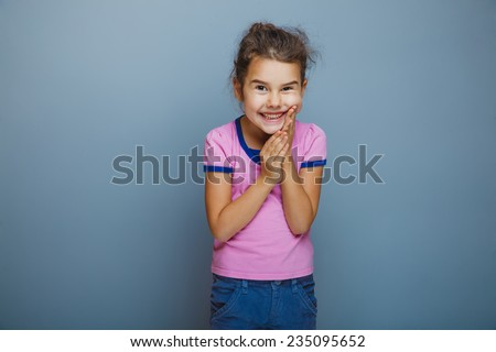 Teen girl child is happy surprise on a gray background
