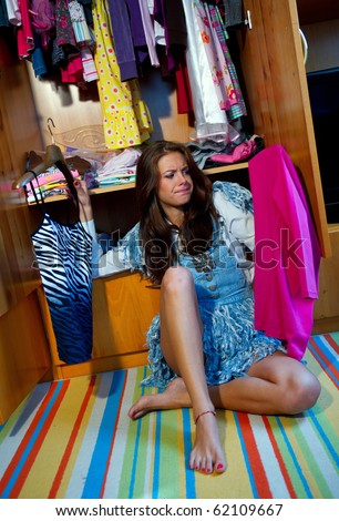 teen girl choosing clothes in front of full closet
