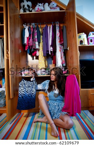 stock photo : teen girl choosing clothes in front of full closet