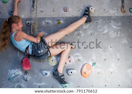 Teen girl climbing a rock wall indoor. Concept of sport life. #791170612
