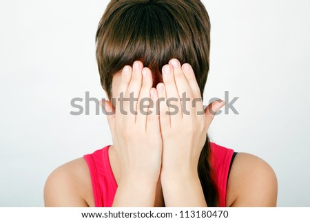 teen girl covers her face with both hands