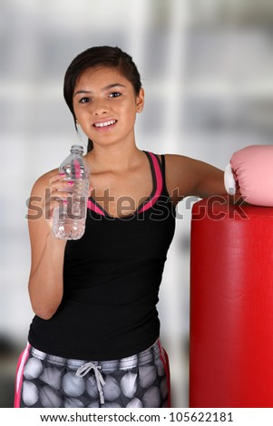 Teen girl drinking water at the gym