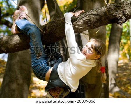 Teen girl hanging on the tree in an autumn park