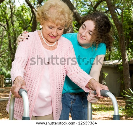 Teen girl helping a senior lady with a walker.
