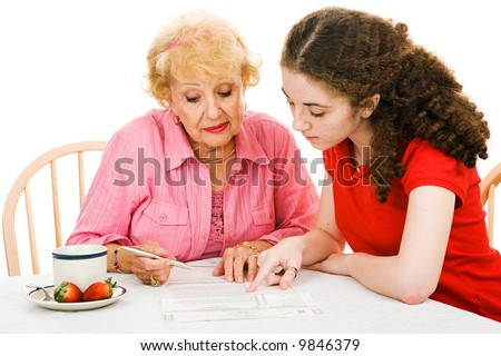 Teen girl helping her grandmother read the fine print on the absentee ballot.  Isolated on white.