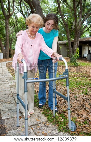 Teen girl helps her aging grandmother to walk using a walker. - stock photo