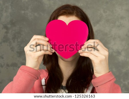 Teen girl holding heart in front of face
