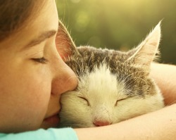 teen girl hug cat close up portrait on the summer garden background