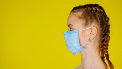 Teen girl in a medical mask in profile looks away on yellow background with copy space. Epidemic precautions. Acute Respiratory Virus Infection. Illness cold flu. Protective mask.