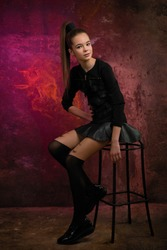 teen girl in high boots short skirt on rusty wall background