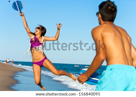 Teen girl jumping at beach tennis ball.