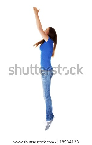Teen girl jumping in air trying to catch something. Isolate don white.
