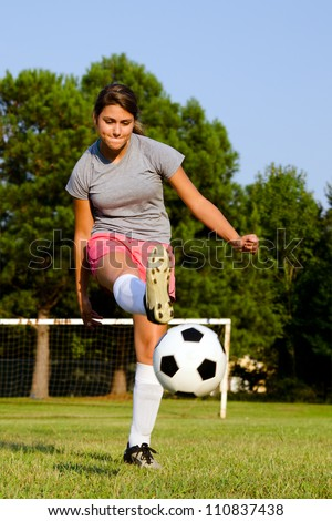 Teen girl kicking soccer ball on field
