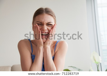 Teen girl laughing holding hands on blush rosy cheeks, happy young woman feeling shy embarrassed making videocall, hysterical laughter of unexpected surprise, strong emotional reaction, head shot