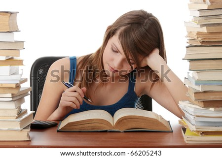 Teen girl learning at the desk, with lot of books around, isolated on white