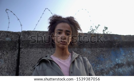Teen girl looking at camera, dreaming to escape prison, juvenile delinquency #1539387056