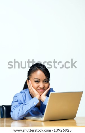 Teen girl looking bored types on a laptop computer as she sits at a desk. Horizontally framed photograph