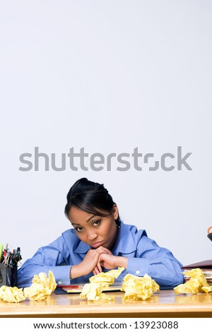 Teen girl looking sad and frustrated as she sits at a desk surrounded by crumpled paper, pens, pencils, and folders. Vertically framed photograph