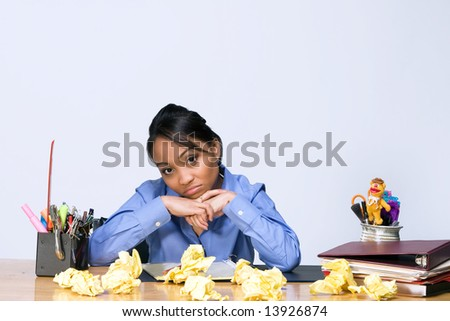 Teen girl looks bored as she sits at a desk surrounded by crumpled paper, pens, pencils, and folders. Horizontally framed photograph