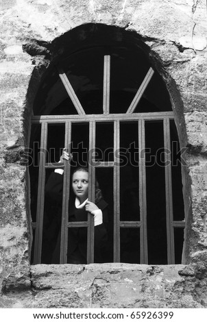 Teen girl looks out of the fortress jail window