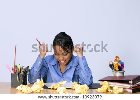 Teen girl looks stressed and angry as she sits at a desk surrounded by crumpled paper, pens, pencils, and folders. Horizontally framed photograph