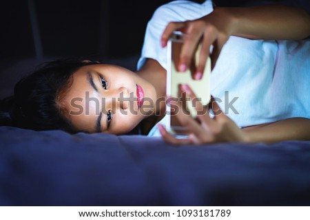 teen girl lying in bed at night and using smart phone