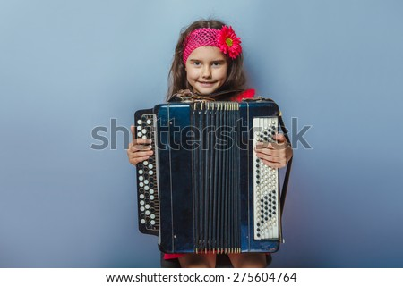 teen girl of European appearance five years holds the accordion in her hands on a gray background