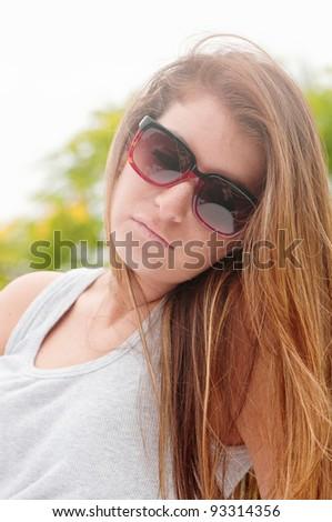 stock photo : Teen girl outdoors wearing sunglasses, a gray tank top, ...