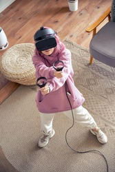 Teen girl pink hair wear vr headset goggles hold controllers play vr video game futuristic immersive simulator virtual reality 3D 360 cyber gaming stand at home look shoot at camera top vertical view.