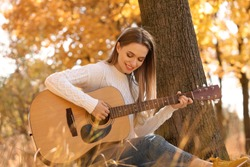Teen girl playing guitar in autumn park