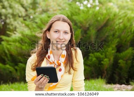 Teen girl reading an electronic book outdoors