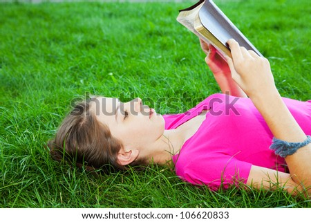 Teen girl reading the Bible outdoors lying on the grass