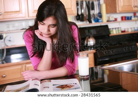 Teen girl relaxing in kitchen with magazine and glass of milk