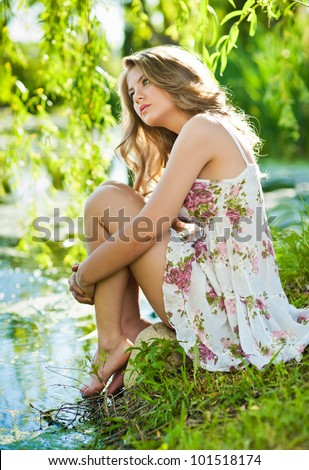 Teen girl relaxing on the shore of lake.