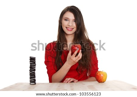 Teen girl sitting at the table and does not know what to eat - apple or cookies.