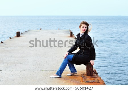 teen girl sitting on the dock in windy weather